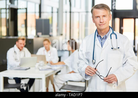 Man as a specialist with competence and experience in front of his medical team in the meeting - Stock Photo