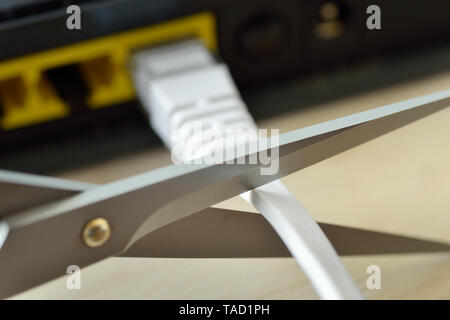 Scissors cutting internet modem router cable - Concept of network and data protection - Stock Photo