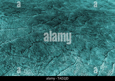 Empty abstract background naturally created by small sea waves in shallow waters and sunlight reflections on water surface. Toned in shades of turquoi - Stock Photo