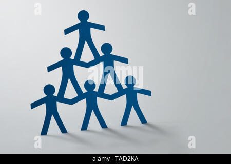 Human pyramid of paper cut-out people on white background - Concept of teamwork - Stock Photo