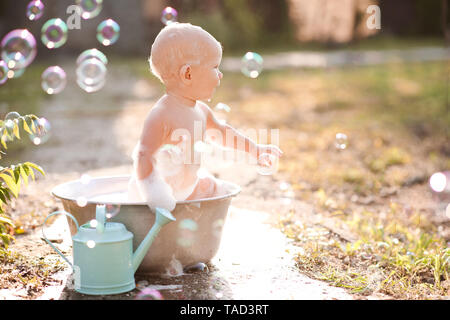 Baby girl washing in bathtub with bubbles outdoors. - Stock Photo