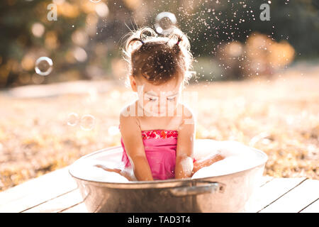 Baby girl washing in basin with soap foam outdoors. Childhood. - Stock Photo