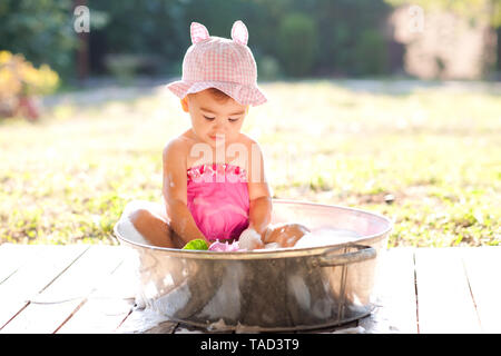 Cute baby girl taking bath outdoors. Playing in bathtub with soap foam. - Stock Photo
