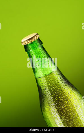 Beer bottle with water drops on a green background - Stock Photo