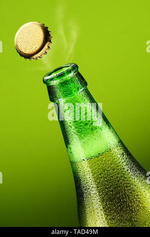 Bottle of beer with opening lid on a green background - Stock Photo