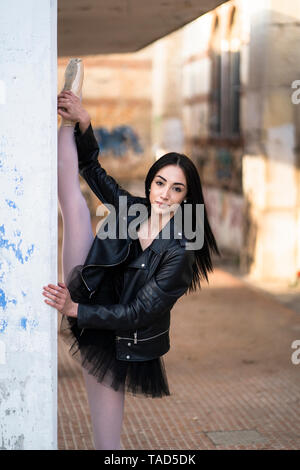 Italy, Verona, portrait of young woman wearing leather jacket and tutu stretching - Stock Photo