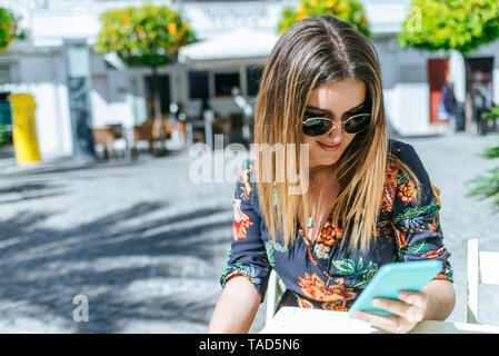 Spain, Cadiz, Vejer de la Frontera, young woman sitting at street cafe  looking at mobile phone - Stock Photo
