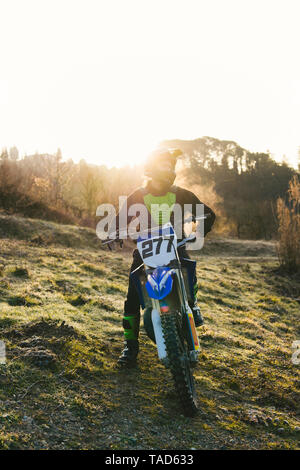 Motocross driver standing on circuit at sunset - Stock Photo