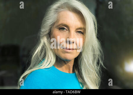 Portrait of content mature woman wearing blue pullover - Stock Photo