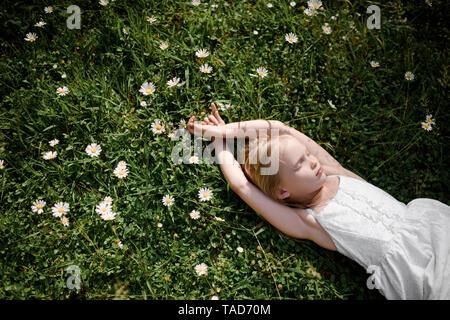 Little girl lying in flower field - Stock Photo