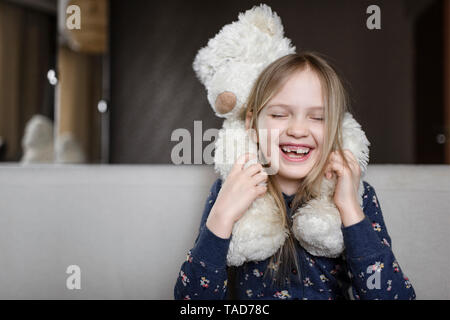 Portrait of laughing little girl with tooth gap holding white teddy bear - Stock Photo