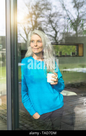 Portrait of content mature woman with cup of coffee leaning against terrace door looking at distance - Stock Photo