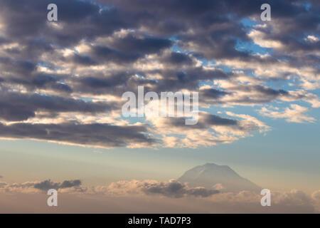 Cloudy faded Mt. Rainier above a foggy haze in daylight - Stock Photo