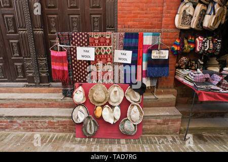 Handicrafts and souvenirs are for sale in a narrow alley off Durbar Square, Bhaktapur, Kathmandu Valley, Nepal - Stock Photo