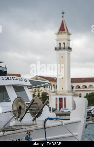 Zakynthos, Greece -  April 2019 : Boat in front of the Saint Dionysios bell tower of the Agios Dionisios church, Zante Island, Zakynthos Town - Stock Photo
