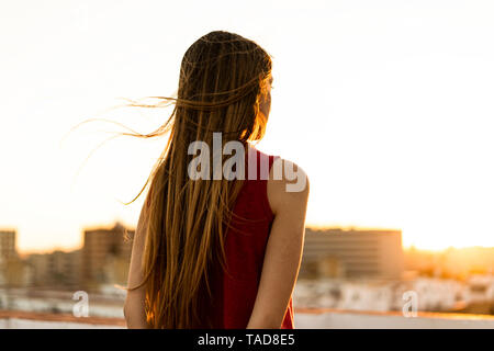 Rear view of teenage girl on roof terrace in the city at sunset - Stock Photo