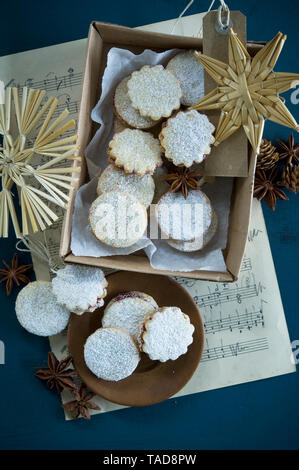 Christmas Cookies Spitzbuben in a box, music sheet, straw stars, star anise, larch cones, gift tag - Stock Photo