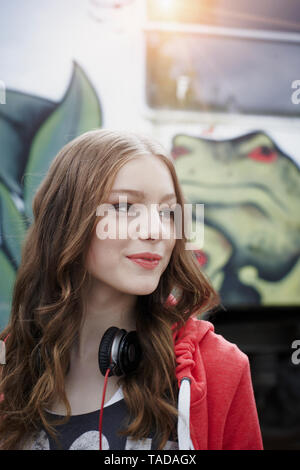 Portrait of teenage girl at a painted train car - Stock Photo