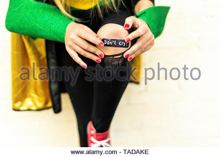 Close-up of band-aid on girl's injured knee - Stock Photo