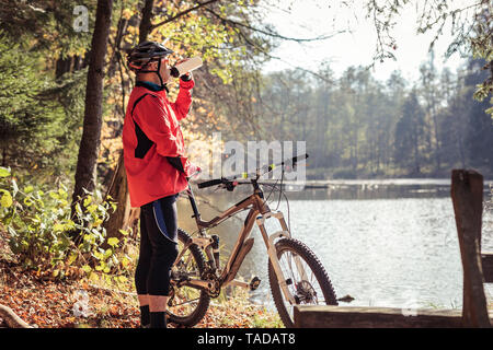 Man with mountainbike having a break at a lake in forest - Stock Photo