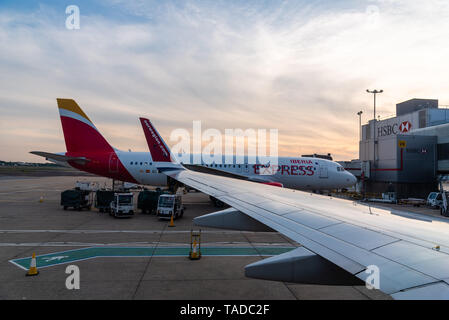 London, UK - May 15, 2019:  Airplanes in runway of international airport of London Gatwick at sunset - Stock Photo
