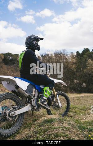 Motocross driver standing on circuit - Stock Photo