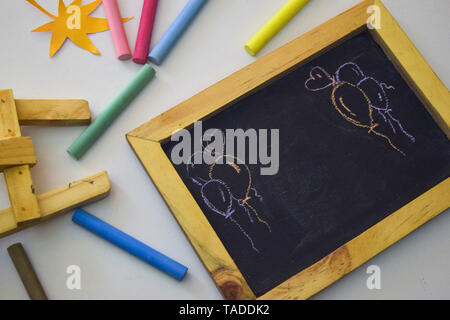 chalkboard with colorful chalk isolated on white background - Stock Photo