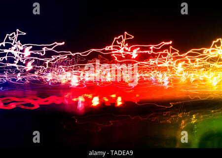 Different light trails of multicolored street lanterns and passing cars scattering in the dark, long exposure urban abstract background - Stock Photo