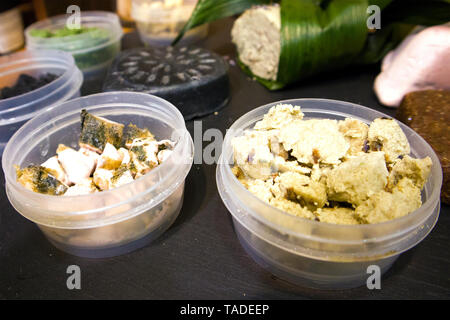 Plastic boxes with pieces of natural cosmetic products and handmade soap arranged on a wooden board - Stock Photo