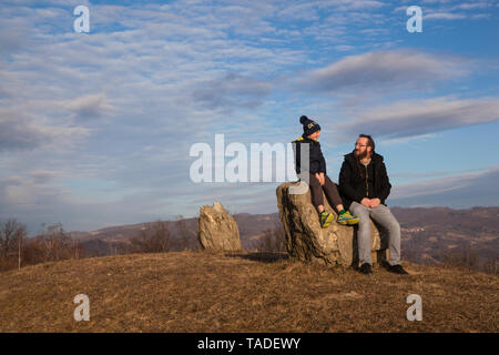 Father and son sitting on a rock and talking - Stock Photo