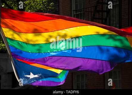 Rainbow flag waving in the shadows with a Puerto Rican gay pride flag at a summer pride parade in New York City - Stock Photo