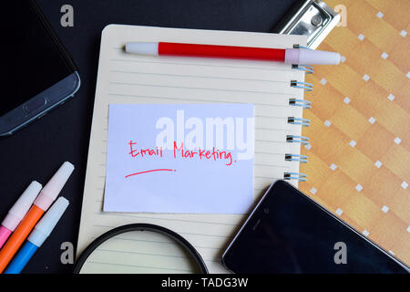 email marketing written on paper isolated on black table - Stock Photo