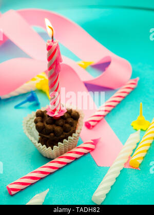 candle on birthday burning in the background other candles, pink ribbons, festive atmosphere - Stock Photo