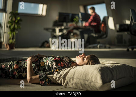 Woman taking a nap, lying on a cushion on the office floor