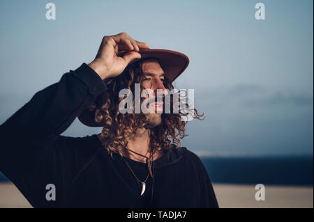 Young man with hat and mustache in the dunes - Stock Photo