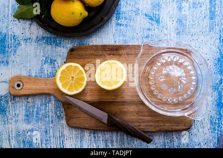 Two lemon halves, kitchen knife and lemon squeezer on wooden board - Stock Photo