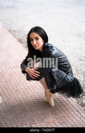Portrait of young woman on tiptoes wearing leather jacket and tutu - Stock Photo