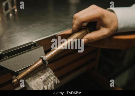Artsisan making jewellery in his workshop, measuring ring - Stock Photo