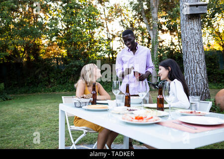Friends at a summer dinner in the garden opening bottle of wine - Stock Photo
