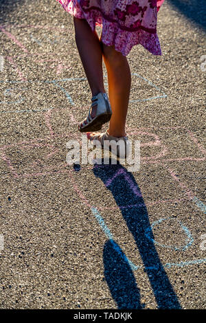 Girl playing hopscotch, partial view - Stock Photo