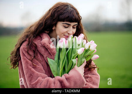 Young woman with bouquet of tulips and pink coat - Stock Photo