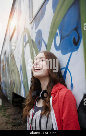 Portrait of happy teenage girl at a painted train car