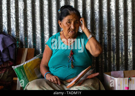 Tibetan exiled woman in refugee camp living in Nepal making a living of weaving on a loom. - Stock Photo