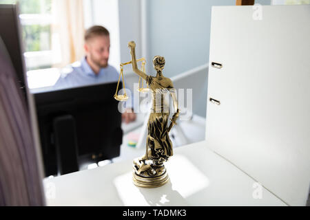 Justice Statue On Shelf And Lawyer Working In Office At background