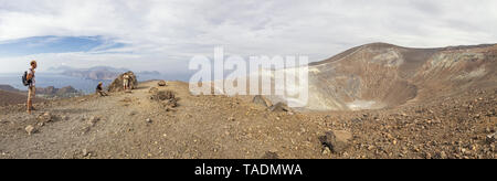 Aeolian Islands, Vulcano, Panoramic view from volcano, Gran Cratere, hikers at volcanic crater - Stock Photo