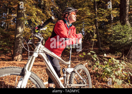 Man with mountainbike having a break in forest - Stock Photo