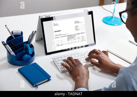 Close-up Of Businesswoman Using Digital Laptop Preparing Invoice - Stock Photo