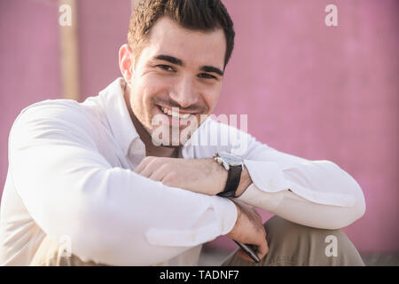 Portrait of smiling young man in front of pink wall - Stock Photo