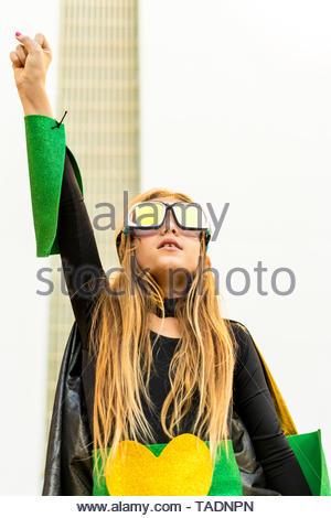 Girl posing in super heroine costume clenching fist - Stock Photo