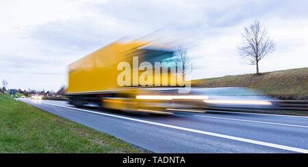 Germany, Badenwurttemberg, Truck overhauling car on federal highway - Stock Photo